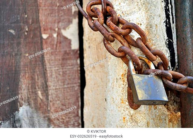 Detail of old, rusty padlock and metal chain. Space in left