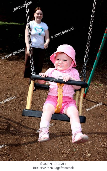Mother pushing baby on swing