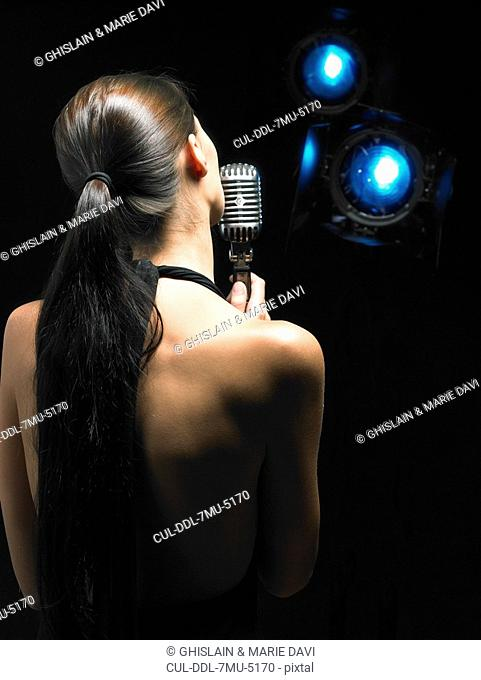Back of woman singing into microphone