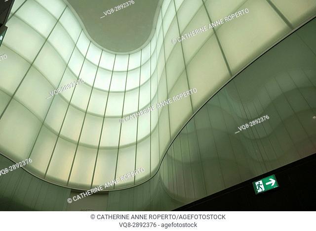 Green and grey undulating wave walls and window reflections, Milan, Italy