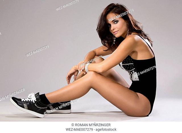 Brunette young woman in lingerie and boots sitting on floor