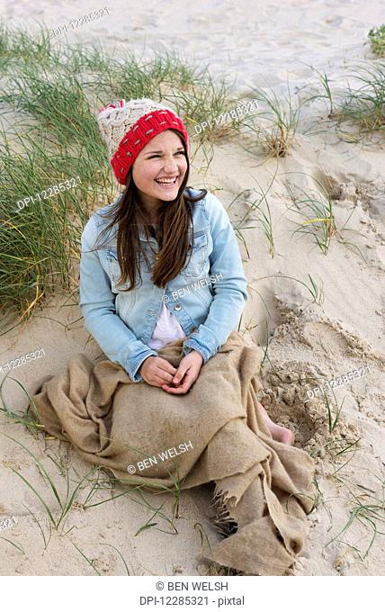 A young woman sits on a beach wearing a knit hat; Tarifa, Cadiz, Andalusia, Spain