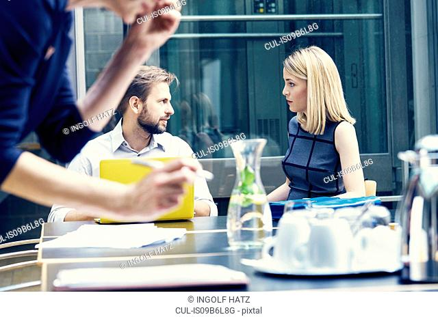 Businesswoman and man having discussion at boardroom table