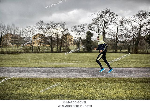 Spain, Man running in park in rainy weather