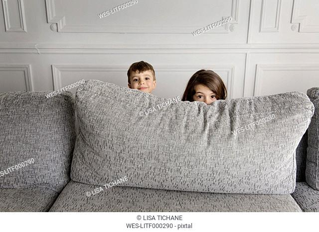 Two little children hiding behind the couch