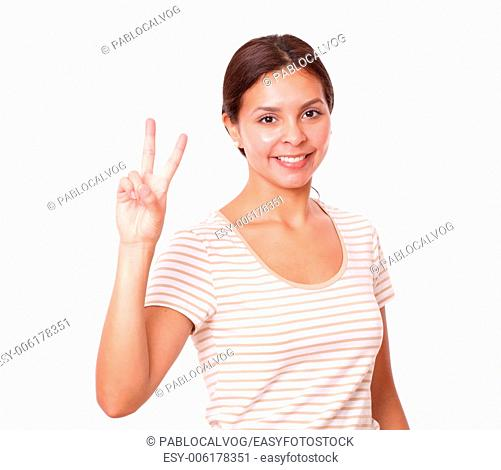 Portrait of pretty young girl with victory sign smiling at you on isolated white background