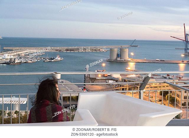 Frau blickt vom 15. Stock des AC Marriot Hotel in Malaga auf die Stadt: Hafen und Küste im Sonnenuntergang, Foto: Robert B. Fishman, ecomedia, 8.11