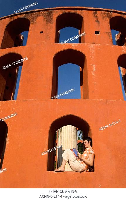 Tourist reading guide book in the Jantar Mantar observatory