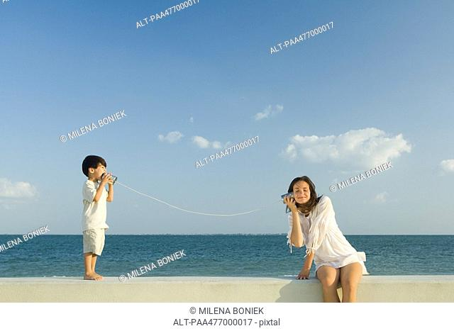 Boy speaking to woman through tin can phone, ocean horizon in background