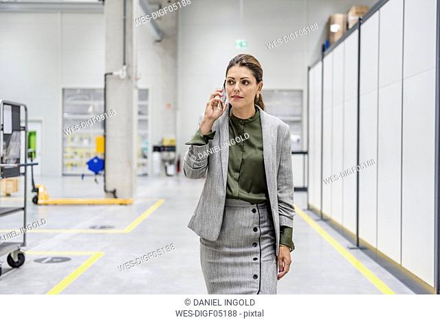 Businesswoman walking in factory workshop, talking on the phone