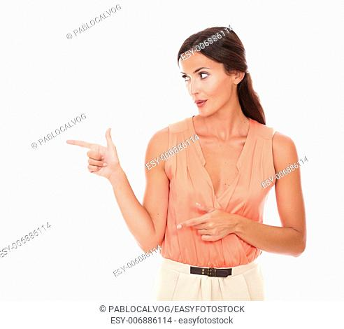 Fashionable lady pointing to her right and looking to her right in white background - copyspace
