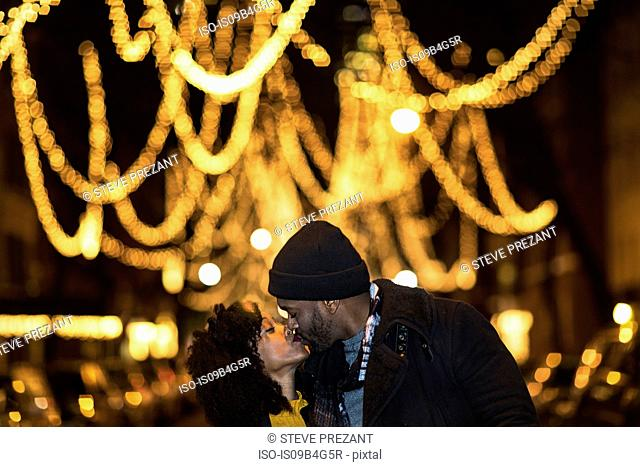 Romantic couple kissing by Christmas lights at night, New York, USA