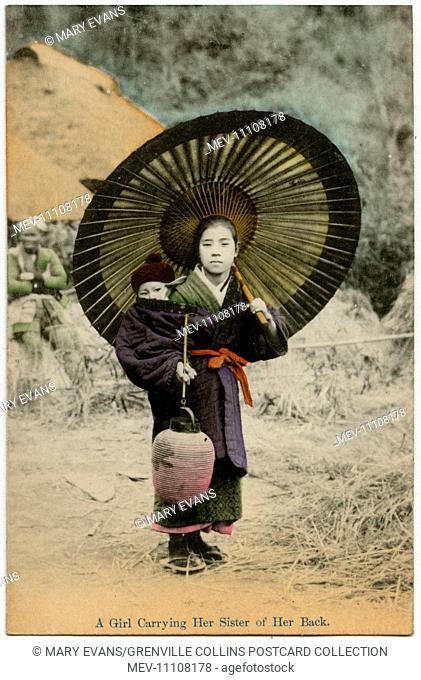 Japan - Girl carrying her younger sister on her back - she is holding a paper lantern in her right hand and a wide parasol umbrella in her left