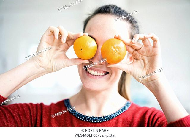 Laughing woman covering her eyes with oranges