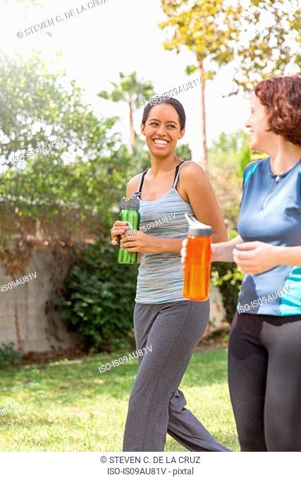 Young women out walking wearing sports clothing carrying water bottles laughing