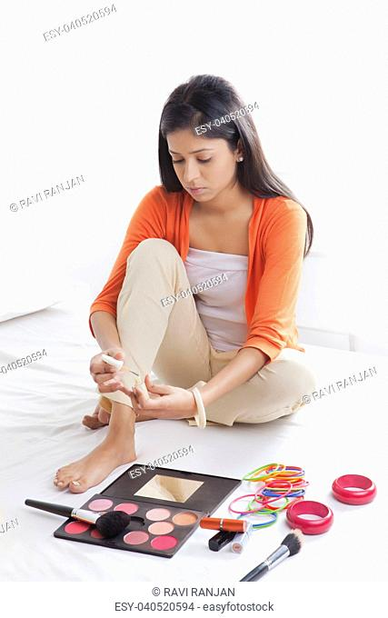 Girl putting nail polish on feet
