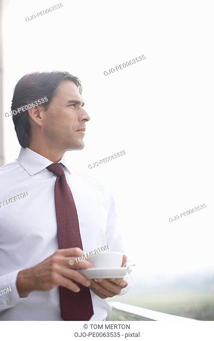 Businessman drinking coffee on balcony