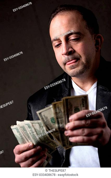 A crooked looking man counting a handful of one hundred dollar bills. Shallow depth of field with focus on the face