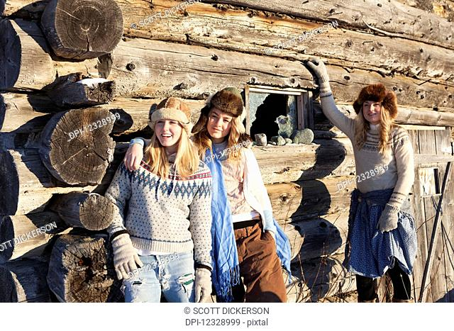 Three Girls Standing Against A Log Wall Wearing Fur Hats; Homer, Alaska, United States Of America