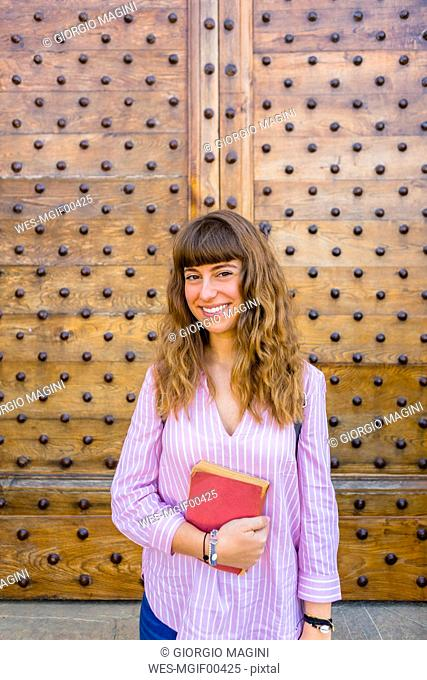 Young woman on a city break, holding guidebook
