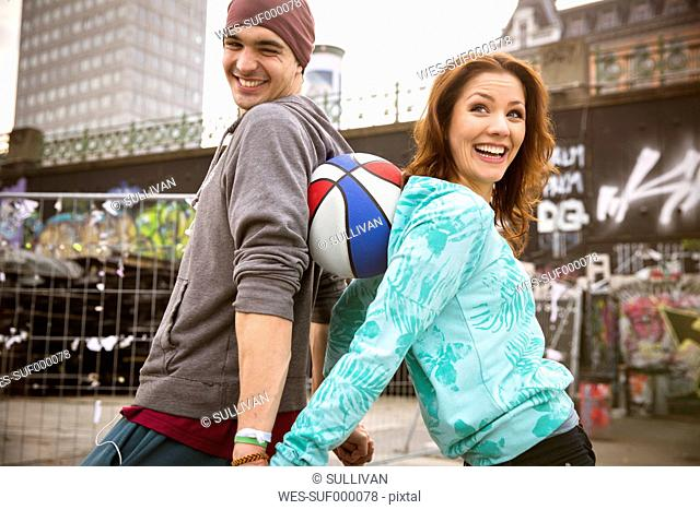 Happy young couple with basketball outdoors