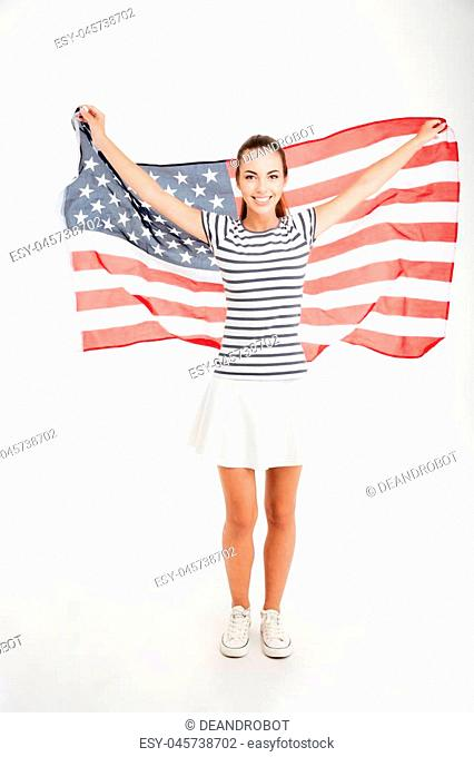 Full length portrait of a happy young girl holding USA flag isolated on a white background