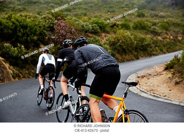 Male cyclists cycling uphill on road