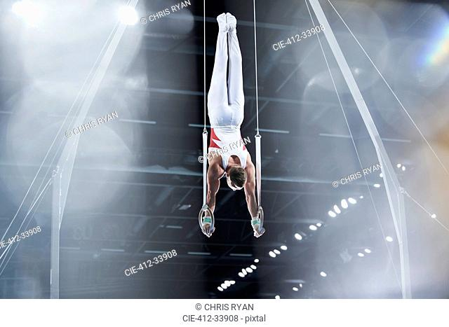 Male gymnast performing upside-down on gymnastics rings in arena