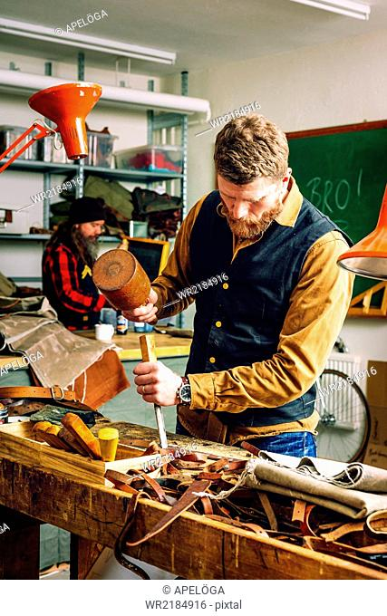 Mature man using mallet and chisel to cut belt in workshop