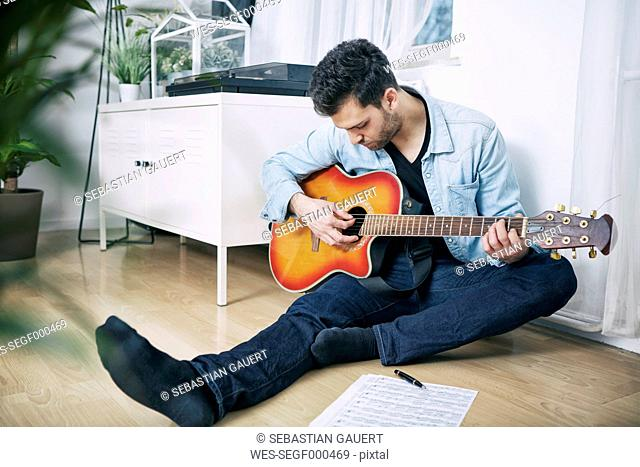 Young man sitting on floor playing guitar