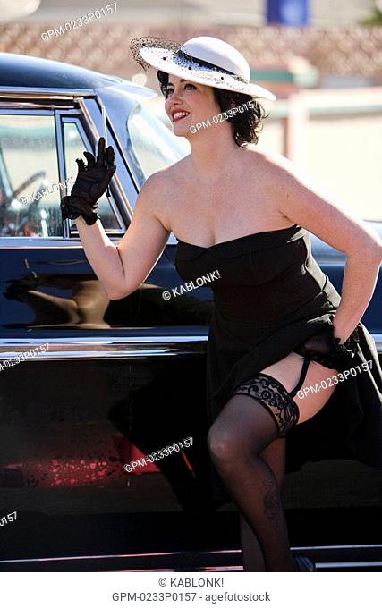 Stylish woman in black standing next to old-fashioned car in sensual pose and holding cigarette holder