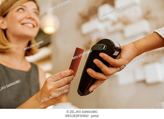 Smiling woman paying contactless in cafe