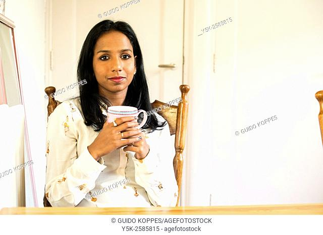 Tilburg, Netherlands. Young, dark colored woman drinking a warm cup of thee, while sitting at her kitchen table