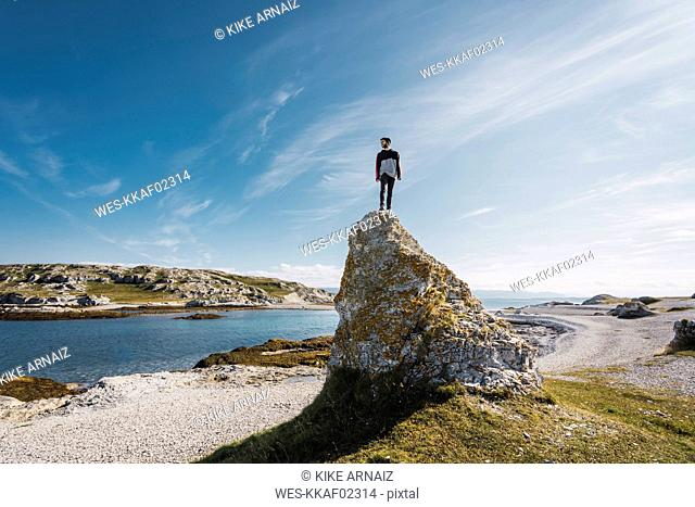 Finland, Lapland, man standing on top of a rock at the coast