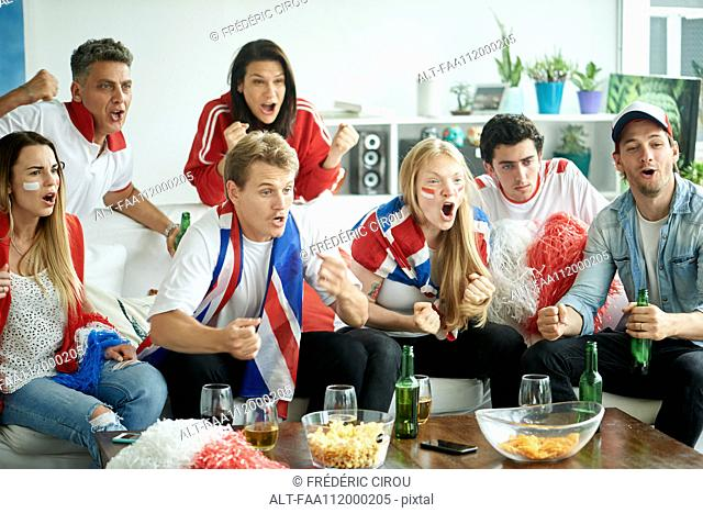 English soccer fans watching match together at home