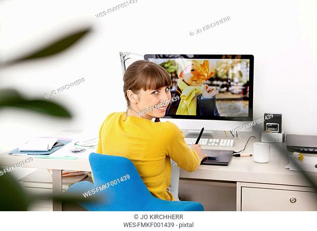 Woman at desk with photo oy boy on computer screen