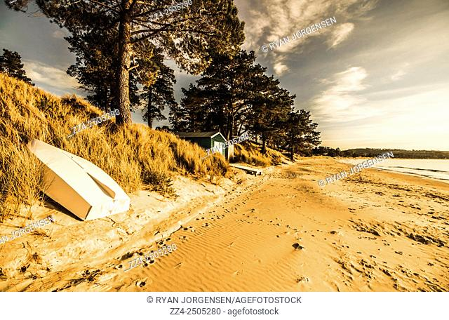 Warm summer scenery of a Southern Australia coast with rowboat and distant sheds. South Arm, Tasmania, Australia