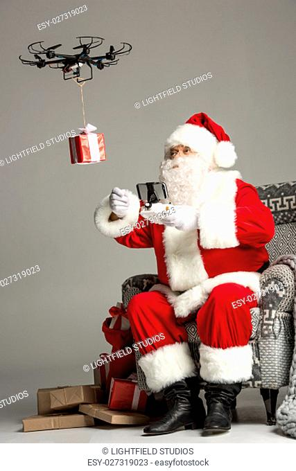 Santa Claus, sitting on grey armchair, using hexacopter drone