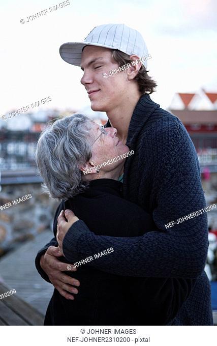 Young man hugging grandmother