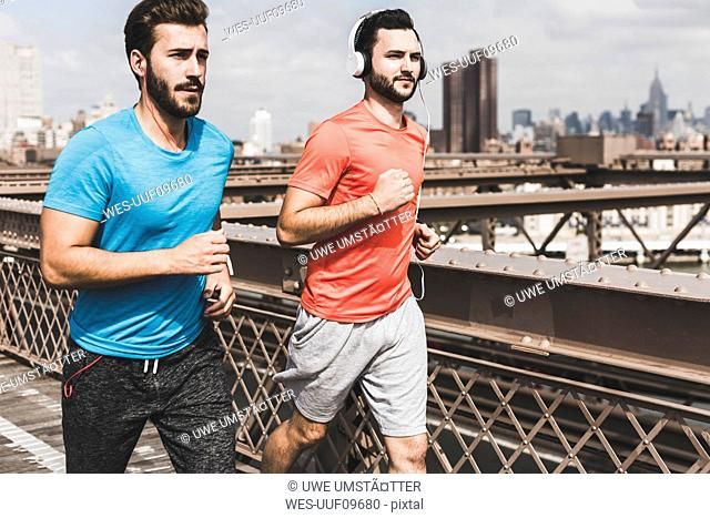 USA, New York City, two men running on Brooklyn Brige