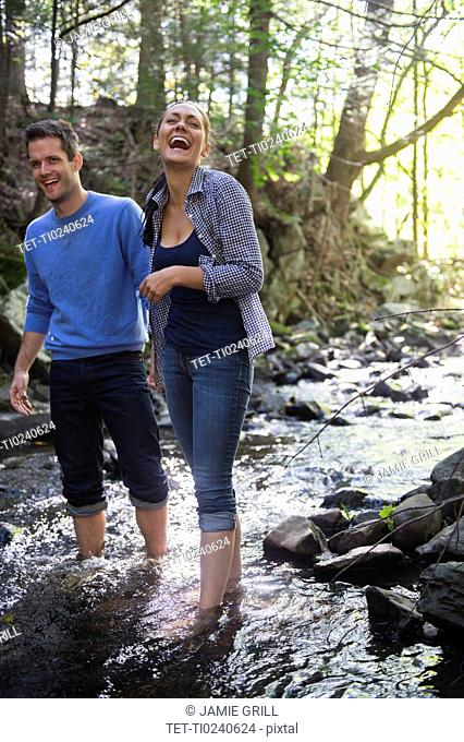 Couple wading in stream