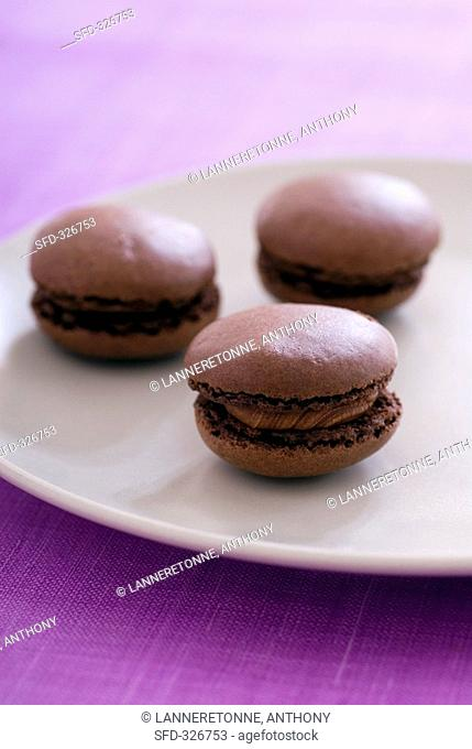 Three filled chocolate macarons