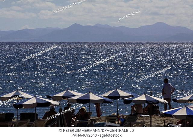 Tourists enjoy the sun on the sand beach of Puerto del Carmen on the Canary Island Lanzarote, Spain, 09 October 2015. Photo:Peter Zimmermann - NOWIRESERVICE...