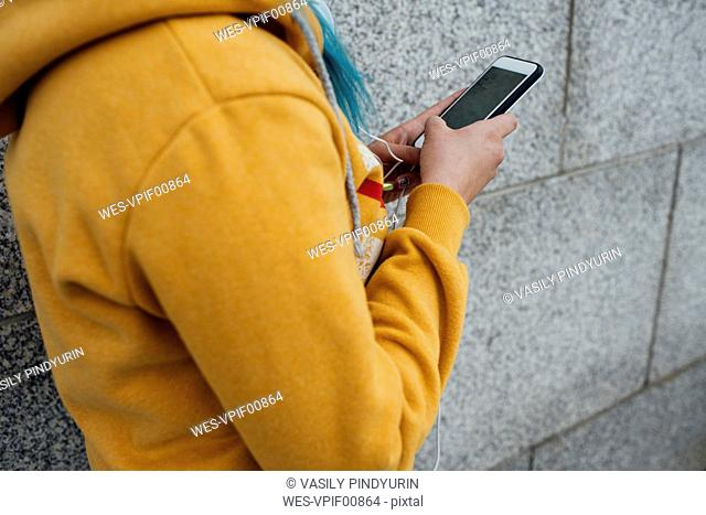 Young woman with dyed blue hair using smartphone, partial view