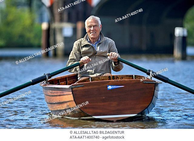 Senior riding a rowboat