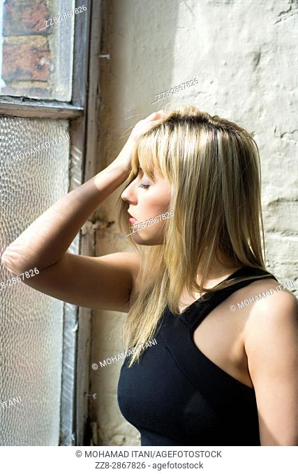 Stressed young blond woman head in hand leaning against the window