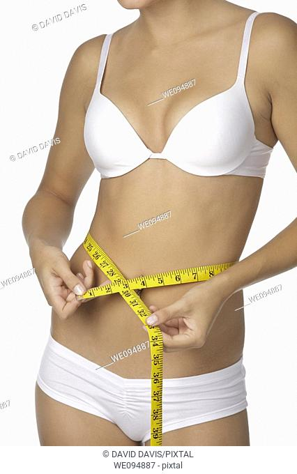 Caucasian woman measuring her waist on a white background