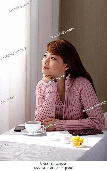 Young woman sitting at table looking our window