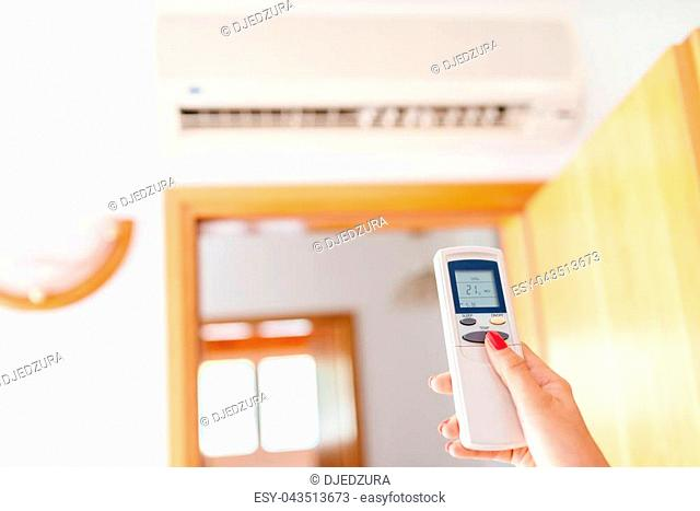 Close up on hand adjusting temperature of home air conditioner with remote control