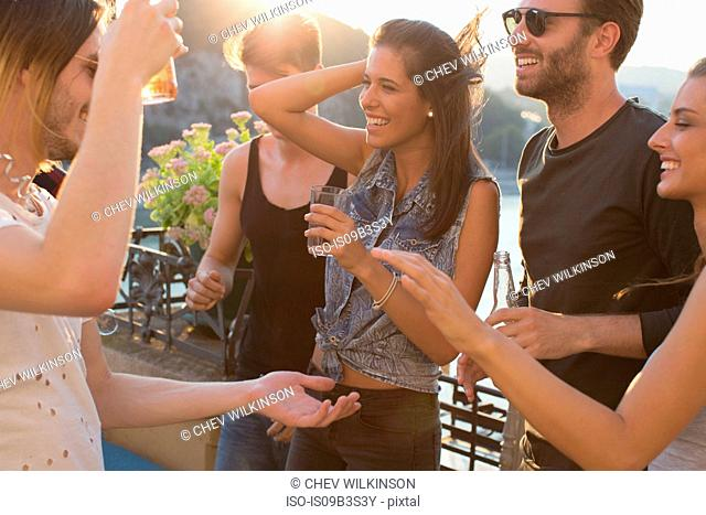 Adult friends laughing at waterfront roof terrace party